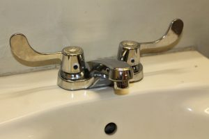 """googly eyes are placed on the faucet in a restroom, giving the faucet a """"personality."""""""