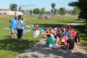 a group of students sit on the ground outside as two teachers explain the rules of an outdoor learning activity