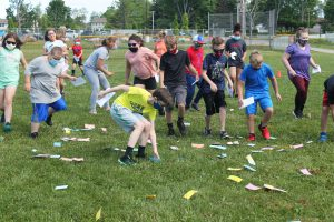 students race to collect fake money that was spread out on the lawn during an outdoor activity day.