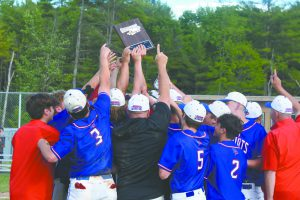 a baseball team wearing red, white and blue surround their coach who is holding up a plaque commemorating a sectional win.