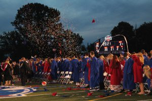 a group of graduates celebrate by throwing their caps in the air, while confetti falls around them