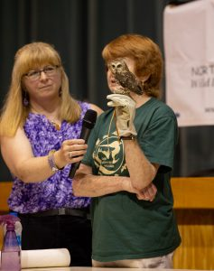 a woman holds a microphone for another woman as she holds a small owl during a student assembly