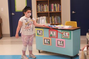 a young girl wearing a face mask uses a pointer to help explain music class rules