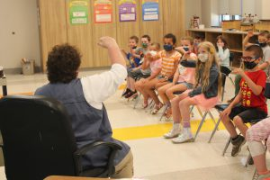 a woman sitting down teaches her students musical concepts