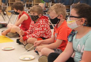 students use chopsticks on paper plates to simulate playing the drums
