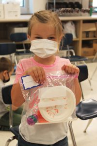 a young female student with blonde hair wearing a face mask and pink t-shirt holds up a plastic ziploc back that holds her makeshift musical instruments