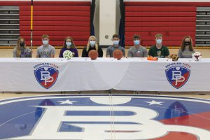 eight student athletes all wearing face masks sit at a B-P branded table in the school's gym