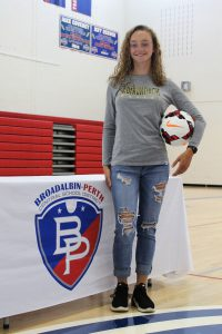 a teenaged girl with long curly hair holding a soccer ball and wearing a greay t-shirt stands in front of the B-P logo