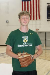 a teenaged boy wearing a green t-shirt and a baseball glove stands in front of the American flag