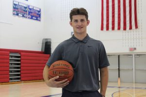 a teenaged boy wearing a grey button up shirt and holding a basketball poses in the B-P gymnasium