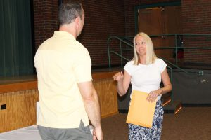 a blonde haired woman wearing a skirt and a white shirt receives an award from a man in a yellow shirt