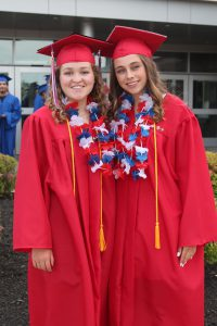 two teenaged girls wearing red graduation cap and gowns with red, white and blue flower leis and a yellow cord wrapped draped over their shoulders stand outside the B-P school.