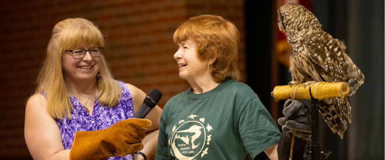 a woman holds a microphone for another woman as she stands next to a large owl