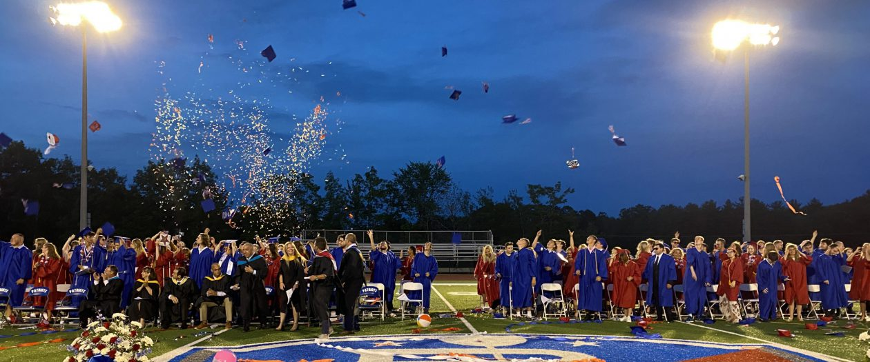 caps and confetti in the air over a group of graduating high school seniors
