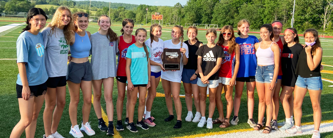 several female athletes pose together on a field, holding a tournment plaque
