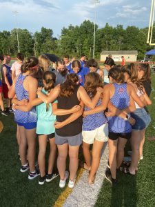 female teammates join arms in a circle on an outdoor field