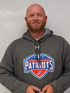 a bald man with a beard, wearing a grey hooded sweatshirt with the BP logo poses in front of a white wall
