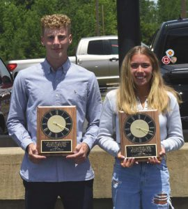 a teenage boy and girl pose next to each other holding plaques