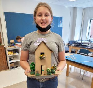 a female student wearing a black face mask around her neck holds up a house made of cardboard