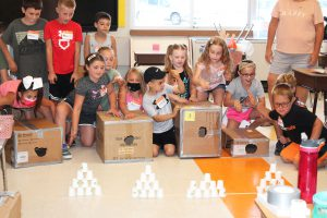 a group of students prepare to do an experiment using cardboard boxes with holes in them and paper cups in the shape of a pyramid.