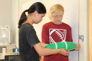 a boy and girl work together on a project involving a green balloon