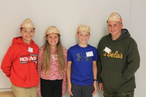"""four students pose with """"brain hats"""" made out of paper"""