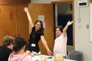 a teacher and student pose with their arms in the air