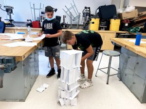 two boys create a building made of paper