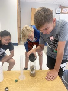 students do an experiment together and watch a bottle closely waiting for a reaction