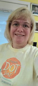 a blonde woman with glasses wearing a yellow t-shirt smiles at the camera